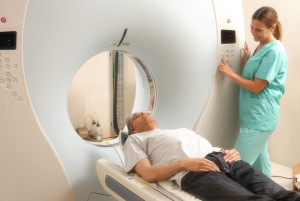 Young female doctor examining man in 40s with CT scanner. Comput